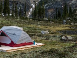 tent camped by a small lake amongst mountain scenery