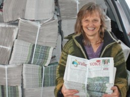 'The Valley Voice' newspaper held up in front of car stacked full of newspapers