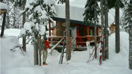 man with skiis outside snowy backcountry lodge