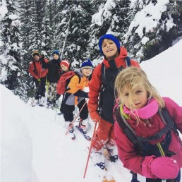 group of children skiing in backcountry